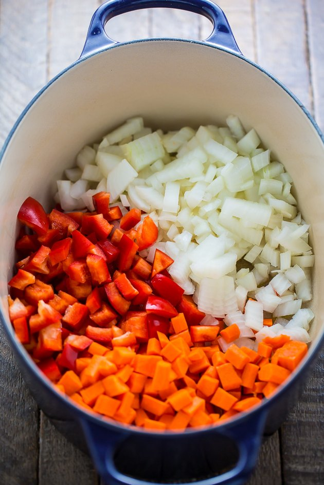 In a soup pot combine onions, carrots, and red bell peppers.