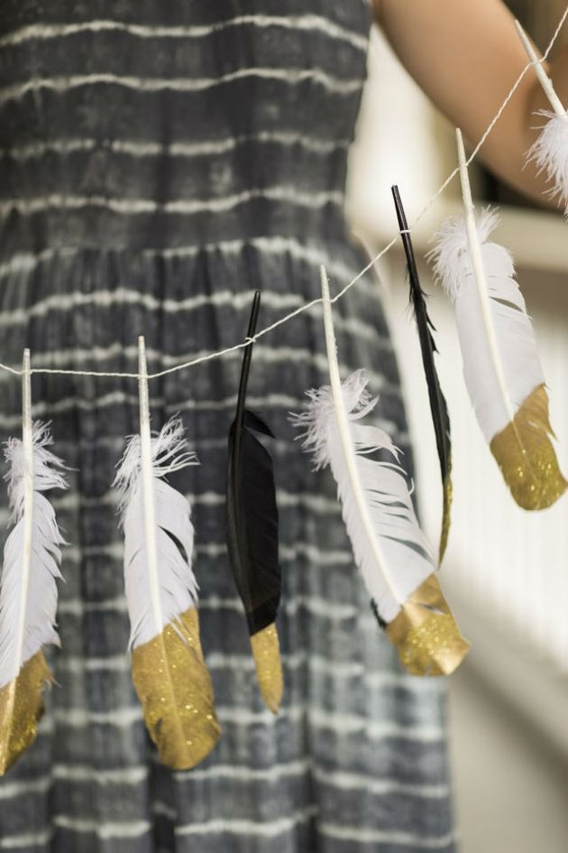 Black and white feathers with the ends painted gold tied into a garland