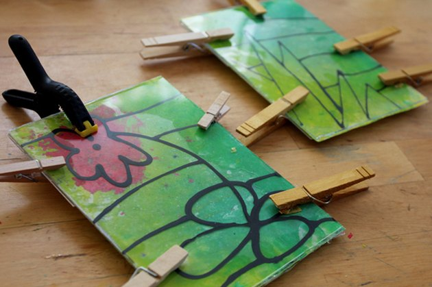 Acrylic and melted crayon art clamped together while drying