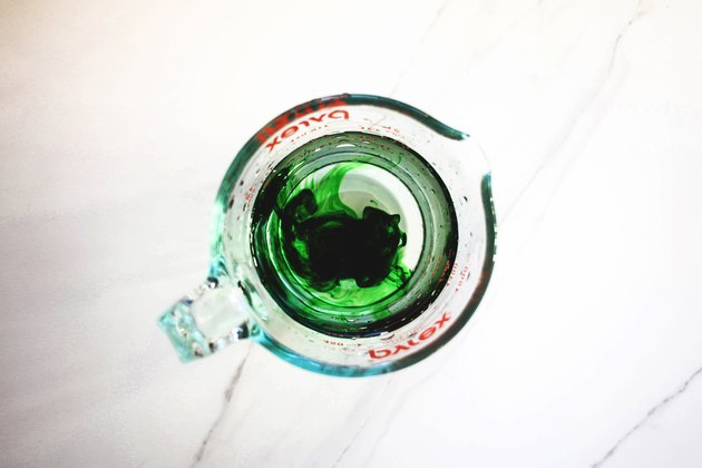 Test the green food coloring by placing a few drops in a jug of water.