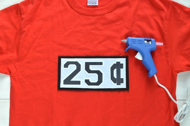 Hot glue the 25 cents sign onto the T-shirt
