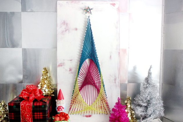 A blue, pink, and yellow string art tree on a white background