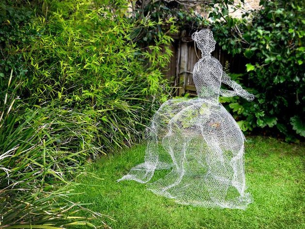 A woman's form made from chicken wire on a lawn