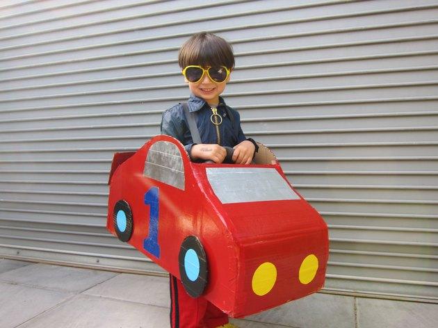 little boy wearing a red race car costume