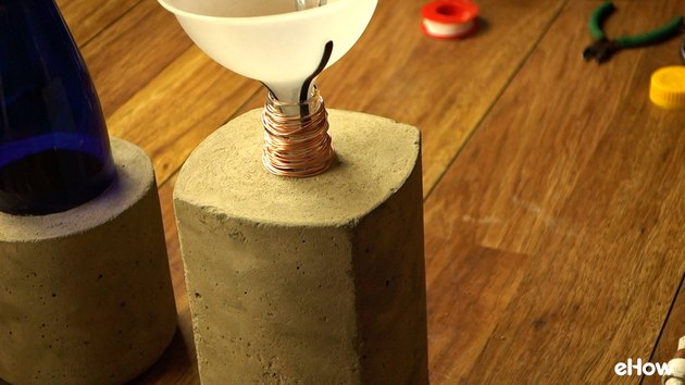 Adding tiki fuel to DIY concrete tabletop tiki torches out of used glass bottles.
