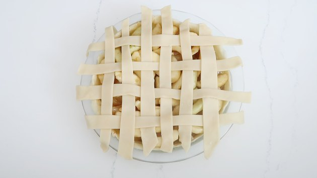 Strips of dough woven into lattice pattern on pie