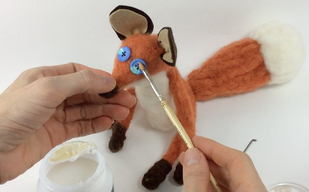 Female hands painting glossy Mod Podge onto the needle felted fox's button eyes.