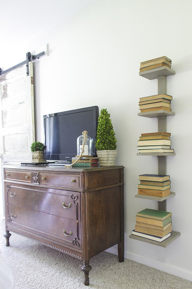 wall mounted spine bookshelf next to antique dresser.