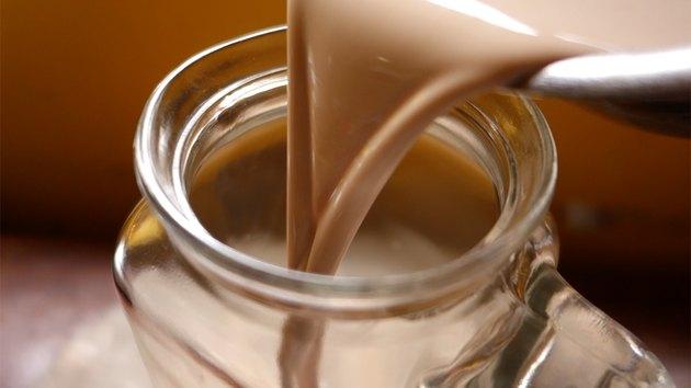 Pouring homemade sugar-free Irish cream liqueur into an airtight beverage container