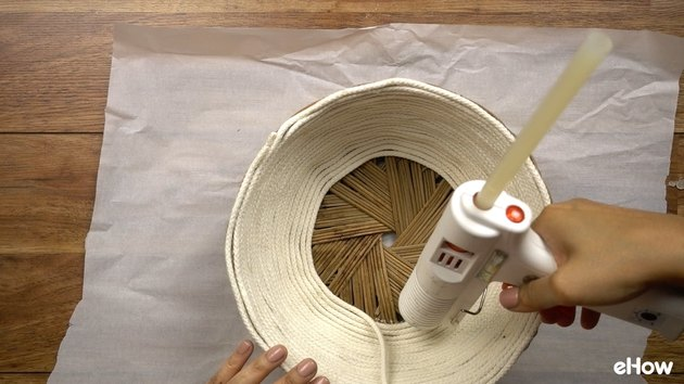 Gluing rope onto basket for DIY desert-style baskets.