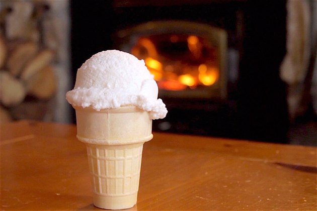 A snow cream cone stands on a table in front of a roaring fire.