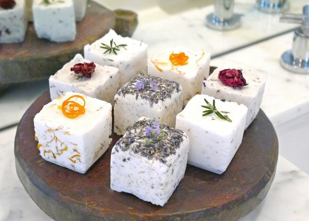 eight bath bombs in various scents displayed on a wood platter