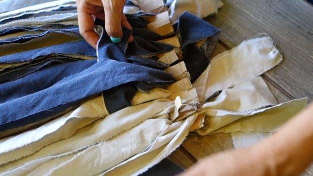 Weaving rag rug using a cardboard loom and fabric scraps.