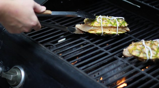 Placing pineapple planks on hot grill