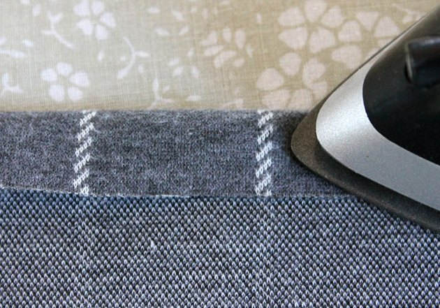 Use an iron to press the hem to the wrong side of the fabric.
