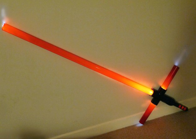 A finished double-blade cross guard light saber lit up against a wall.