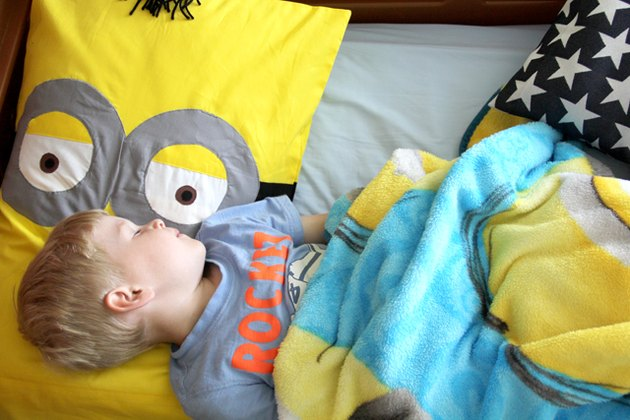 Child sleeping on minion pillow