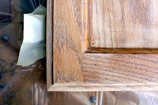 tape off hinges using painters tape | How to Paint Oak Bathroom Cabinets