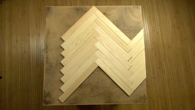 Gluing paint stir sticks to tabletop in herringbone pattern.