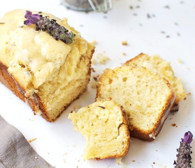 A sliced loaf of lavender lemon ice cream bread topped with lavender flowers