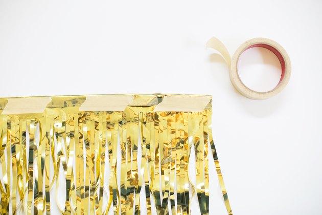 Masking tape on a gold fringe garland