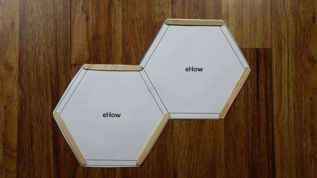 Using a printed template to create popsicle stick DIY hexagon shelves.