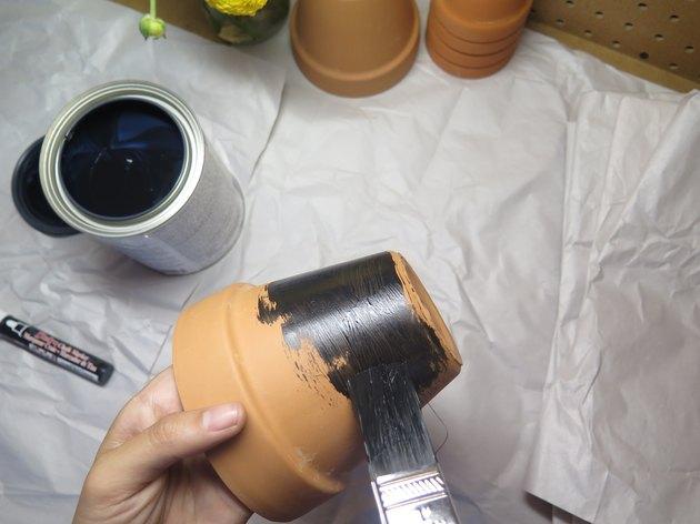 Paint chalkboard paint onto the terra-cotta pot.