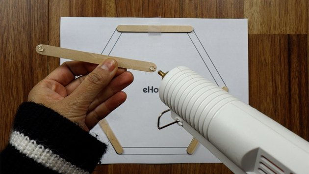 Gluing popsicle sticks for DIY hexagon shelves.