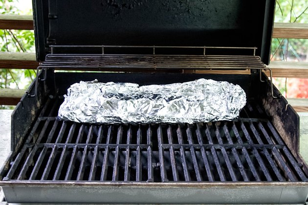 Baby back ribs wrapped in foil on the grill