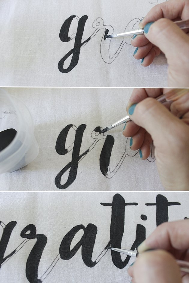 Painting letters on fabric.