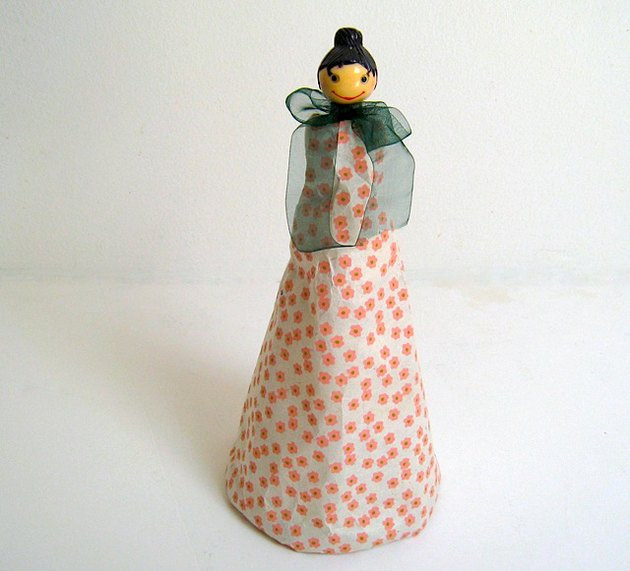 Lady Cheese Grater dressed in tissue paper with a bow tied around her neck