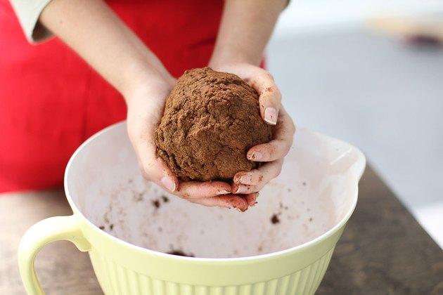 Woman holding ball of cinnamon dough