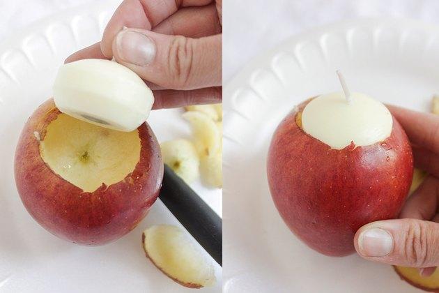 Placing tea light candle into apple
