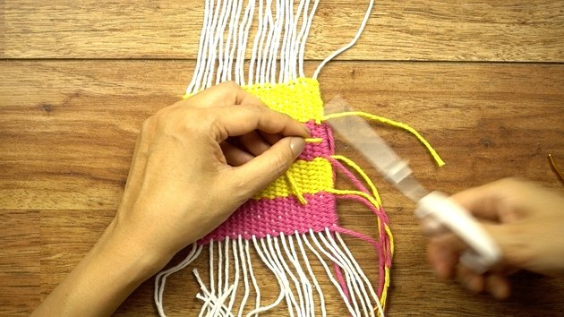 Weaving in loose yarn tails for DIY coasters on a cardboard loom.