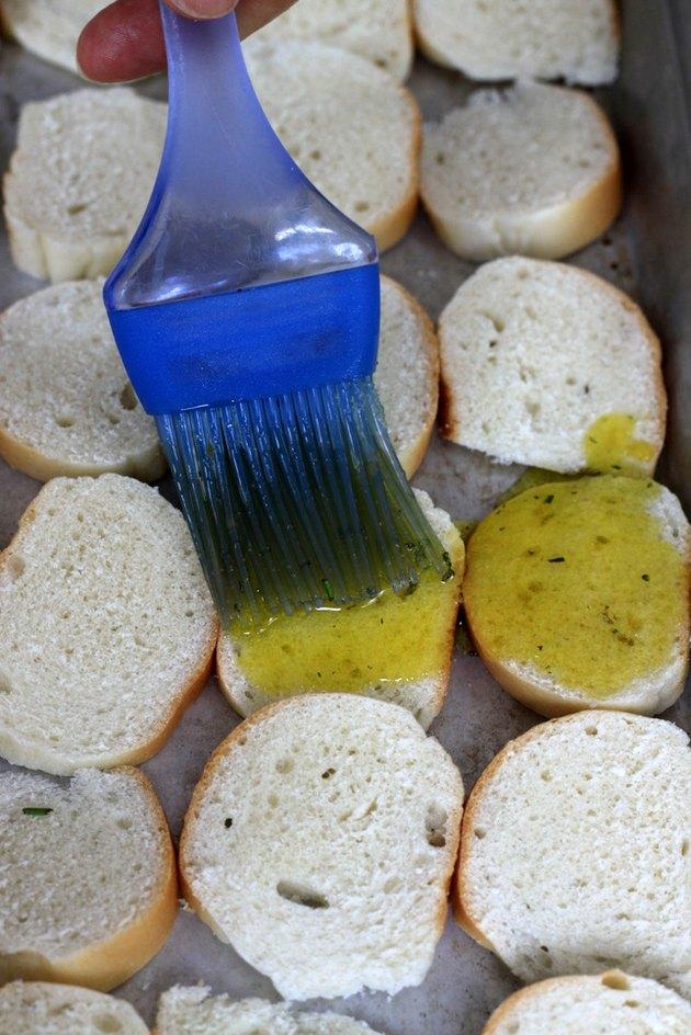 brush oil mixture on bagel chips
