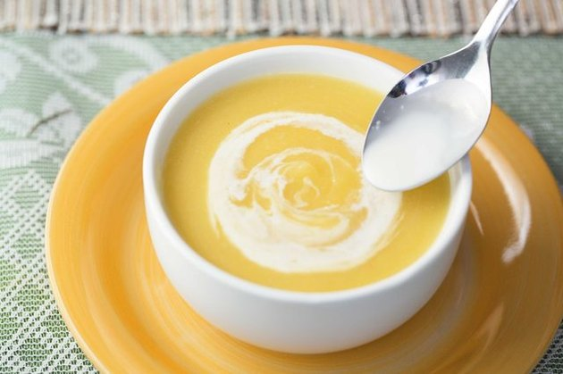 A bowl of orange-tinted pumpkin soup topped with a dollop of cream.