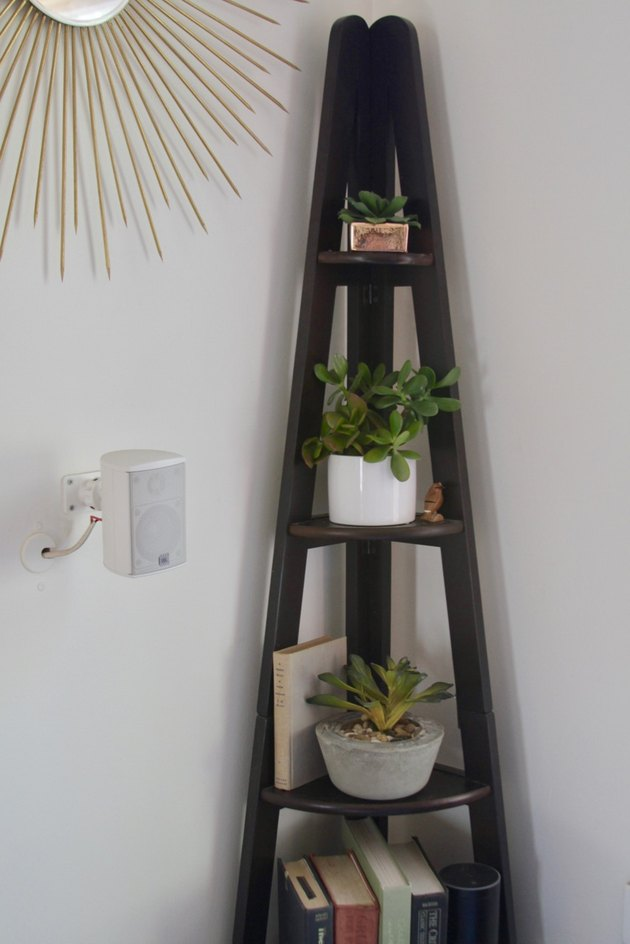 Faux plants on a corner shelf.