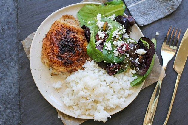 Chicken thigh on a plate with rice and salad