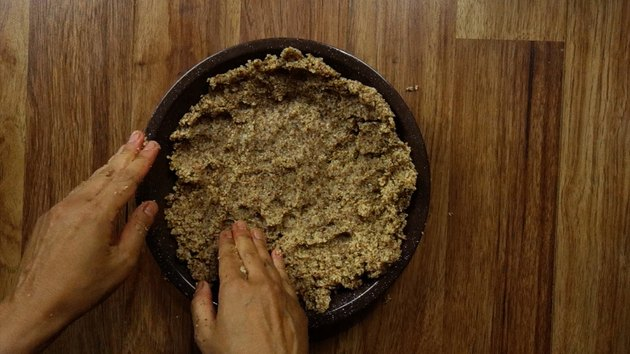 Pressing an almond meal pie crust into a pie pan.