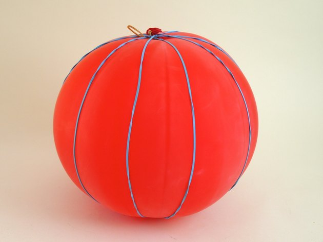 A balloon with several rubber bands wrapped around, dividing it into sections.