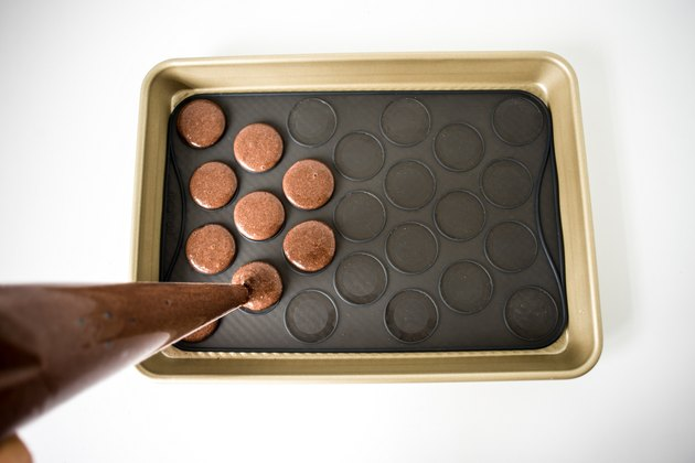 Piping the macarons onto the silicone macaron slip-mat.