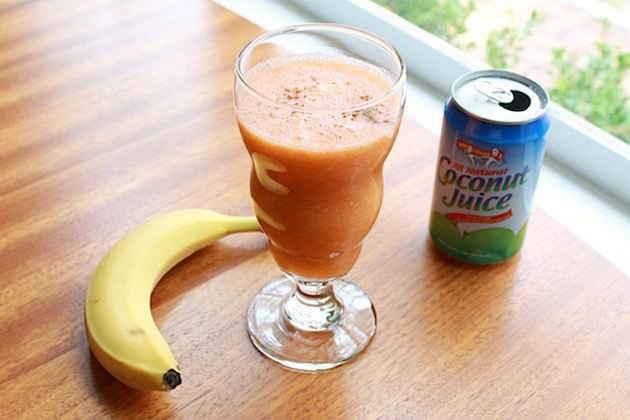 A tropical smoothie with a banana and can of coconut juice on either side.