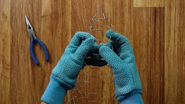 Forming a cone with chicken wire with gloved hands.