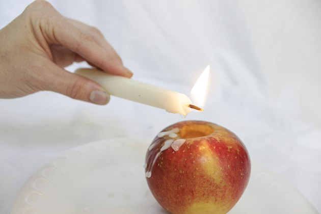 Dripping taper candle wax over apple.