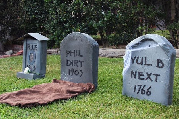 Three cardboard tombstones with silly names