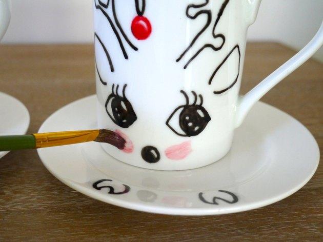 A paintbrush applying red blush cheeks to a mug
