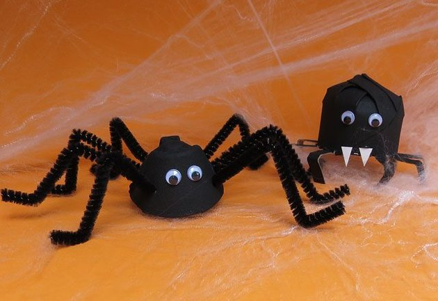 Two black homemade spiders with an orange background