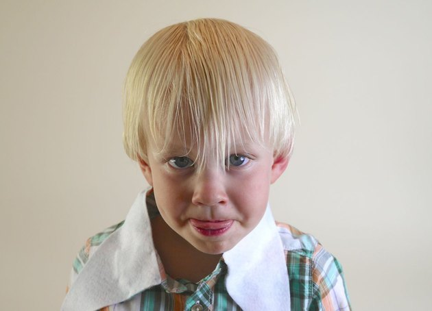 A little blond boy with his hair combed forward.