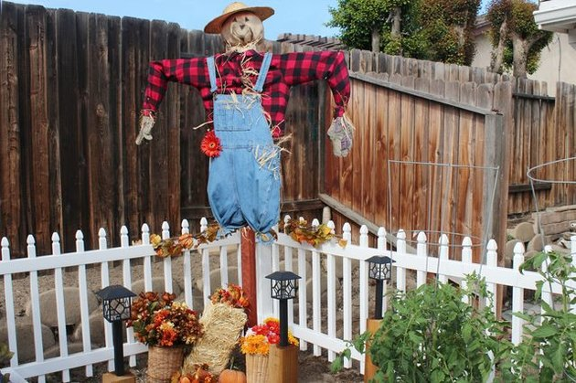 A scarecrow in overalls and a red flannel shirt