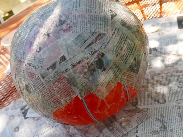 Half of the balloon covered in mache.